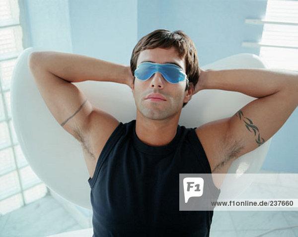 Mann mit Tätowierungen auf seine Arme,  entspannend mit einer Gelmask über seine Augen