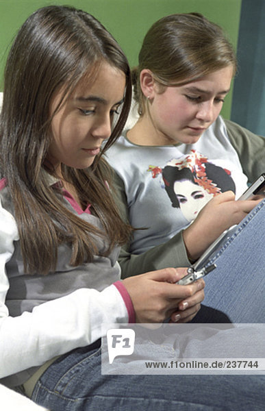 two girls sitting together and writing text messages on mobile phones