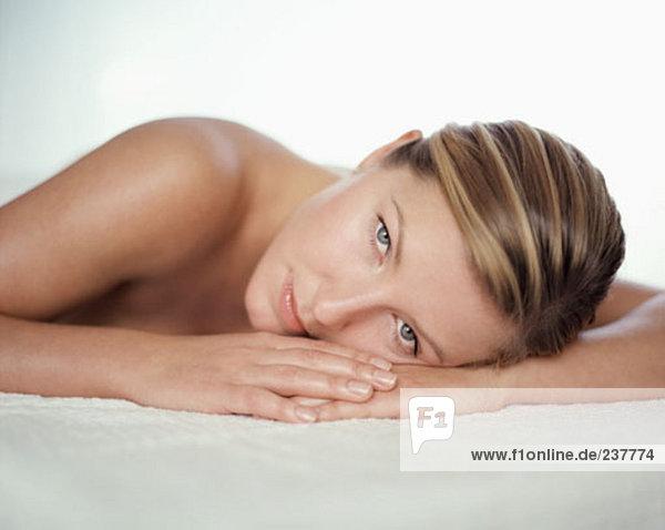 Porträt von nackte junge Frau  hinlegen und Blick in die Kamera