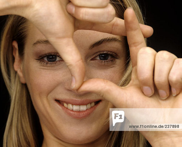 Young Woman looking durch ihre Finger