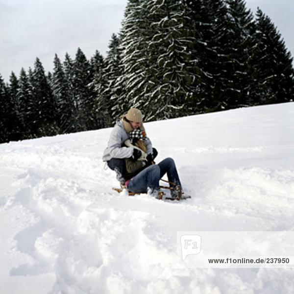 ein Teenager paar Schlitten im Schnee