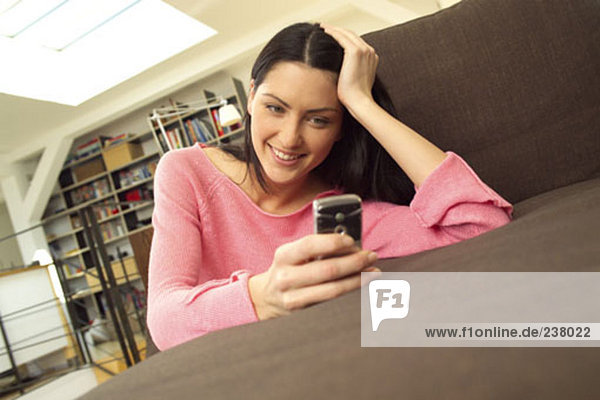 young woman resting on sofa looking at display of mobile phone