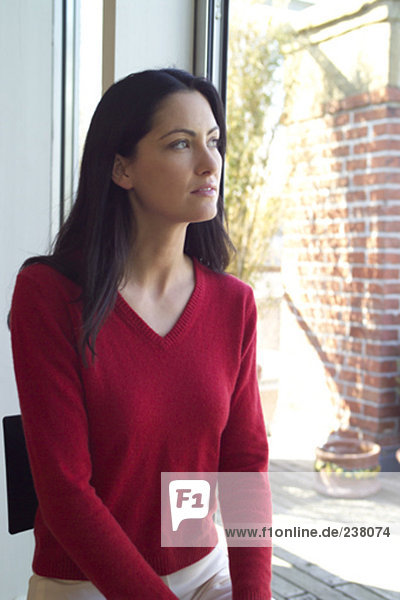 young woman in red jumper looking out of window
