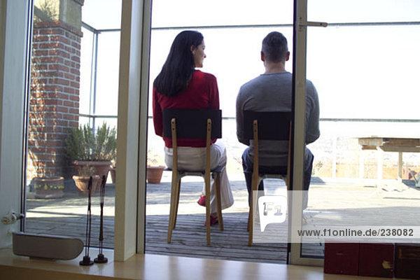 Rückansicht des jungen Paares sitzen auf einem Balkon
