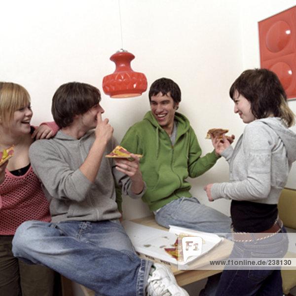 vier Teenager Freunde sitzen zusammen essen takeout pizza