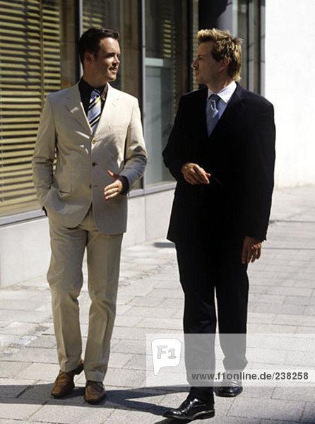 Geschäftsmann machen eine Erklärung an einem Kollegen beim gehen auf der Straße