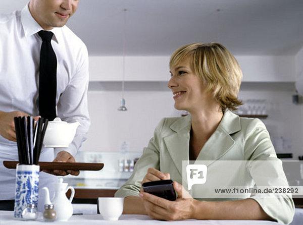 Frau hält elektronischen Organizer während wird serviert im restaurant