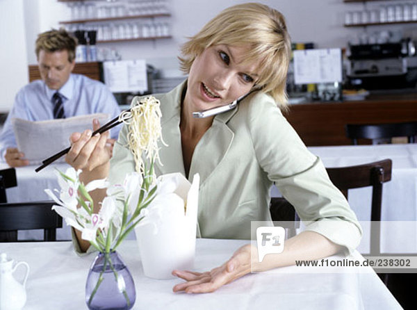 Frau isst Noodles während redend über Mobile; Kaufmann lesen Papier im Hintergrund