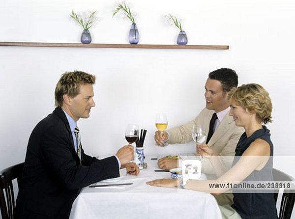 Gruppe von Geschäftsleute an Restaurant Tisch heben ihre Gläser für ein toast