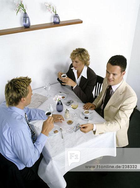 drei Geschäftsleute beim Mittagessen  einer hält eine Kreditkarte