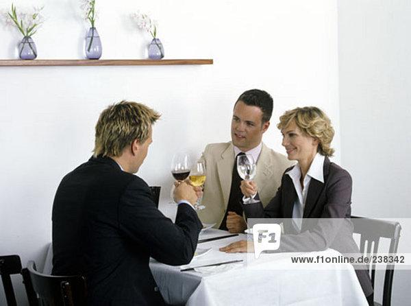Gruppe von Geschäftsmännern und geschäftsfrau erhöhen ihre Gläser zu feiern