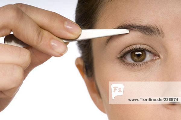 eine junge Frau mit einer Pinzette ihre Augenbrauen zupfen