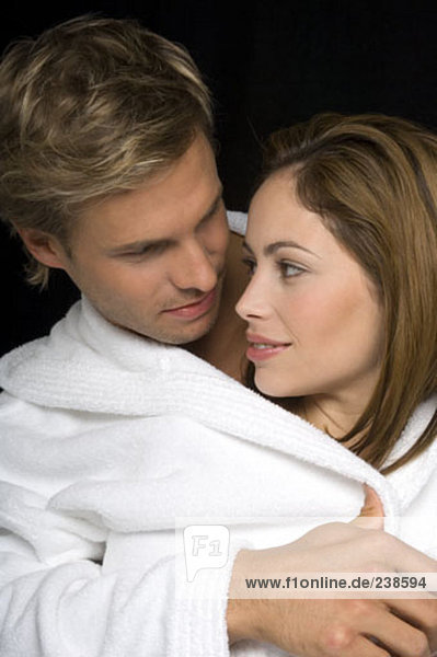 junges paar in Bademäntel umarmt einander