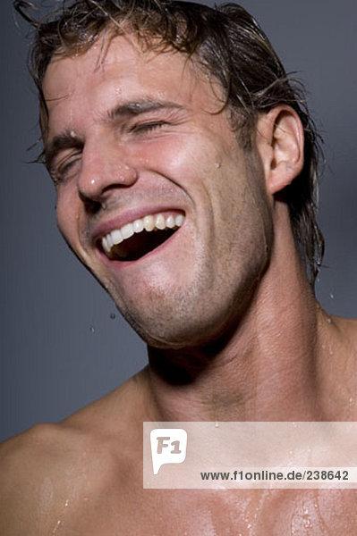 junger Mann lachend beim Duschen