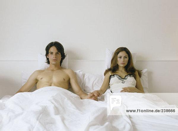 Paar hält hände im Bett  ernsthafte suchen