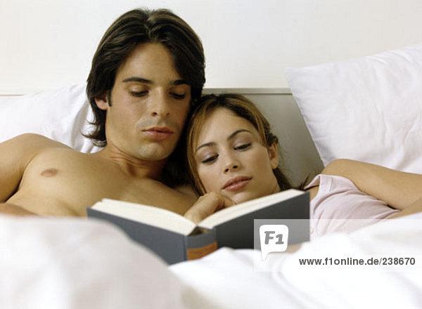 junges paar Lesung Buch zusammen im Bett