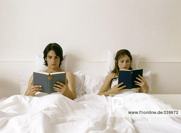 paar liegend im Bett  Bücher lesen