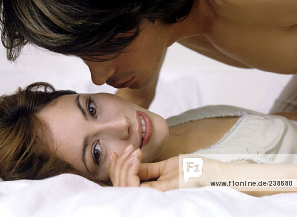woman lying on bed while man kisses her cheek