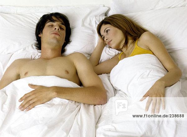 Paar im Bett  junge Frau beobachten schlafende Mann