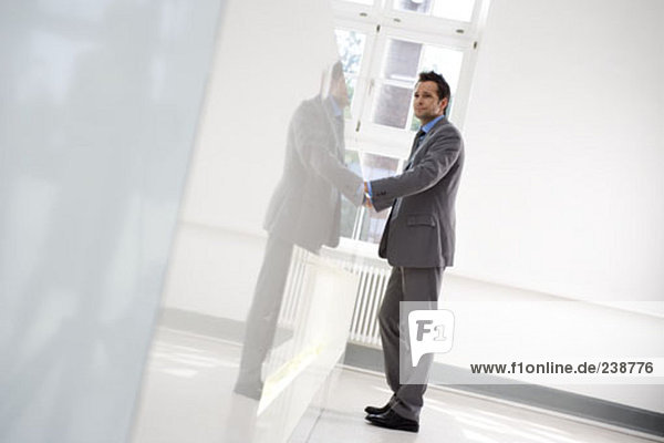 young businessman waiting at reception in office building lobby