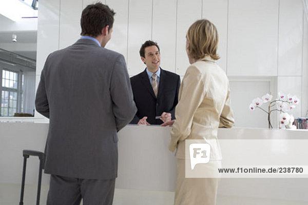 Empfangsdame helfen Geschäftsmann und geschäftsfrau an der Rezeption
