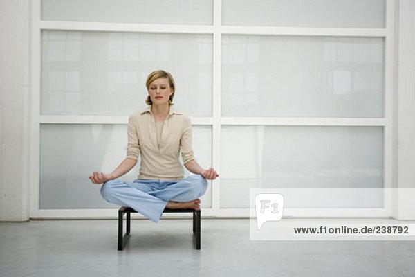 Portrait Ruhe blonde Frau sitzen auf Hocker  doing Yoga und Meditation