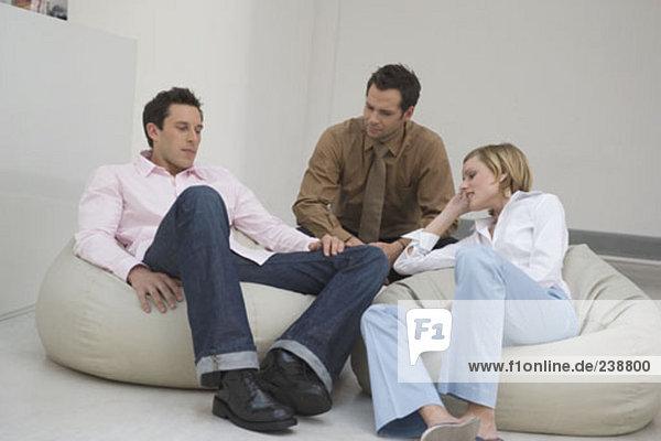 drei Leute sitzen auf Sitzsäcken mit einem Gespräch in entspannter Office-Bereich