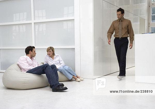 Kaufmann und geschäftsfrau in casual Office-Bereich  miteinander zu reden  während ein anderer Mann zusammen