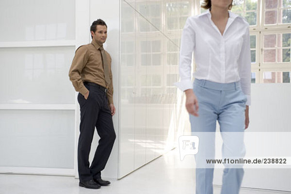 businessman looking at woman and eyeing her up as she passes by in office by