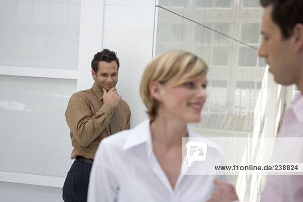 junger Mann hinter dem Rücken der Frau lächelnd engagiert im Gespräch mit Kollegen in office