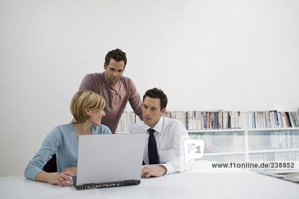 drei Geschäftsleute herumsitzen Laptop in einem Büro
