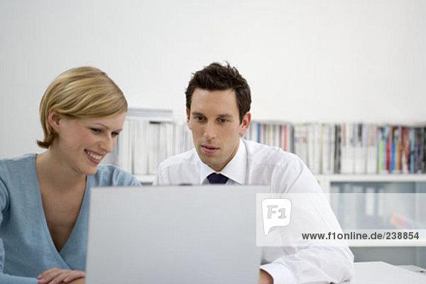 männliche und weibliche Büroangestellte Blick auf Laptop-Bildschirm