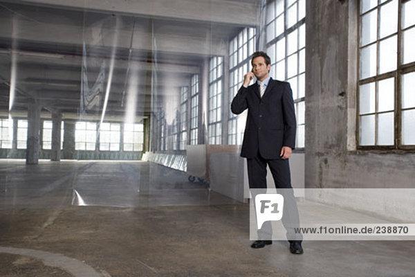 young Businessman mit seinem Handy in leere Fabrikhalle