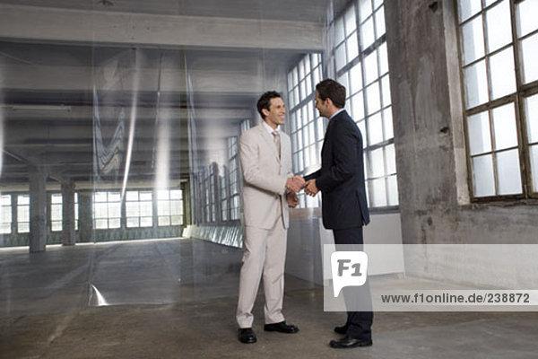 zwei Geschäftsleute Händeschütteln in leere Fabrikhalle