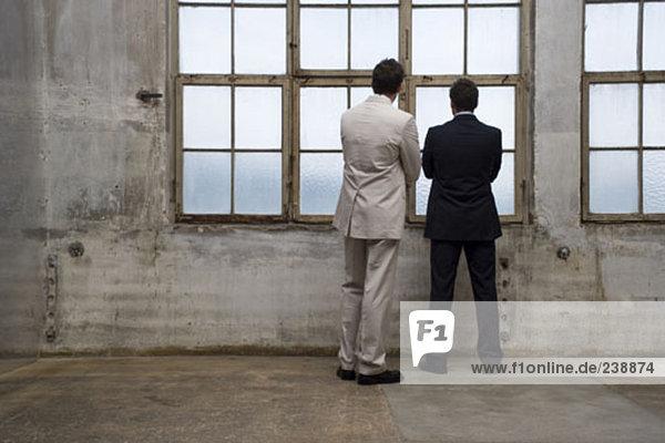 zwei Geschäftsleute Blick aus Fenster in leere Gebäude
