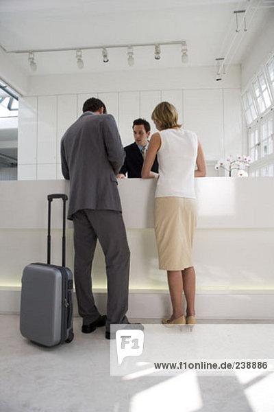 Business Paar steht an der Rezeption und Check-in mit Gepäck