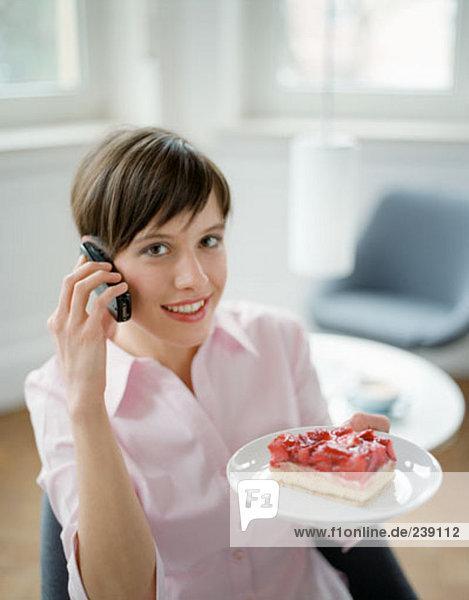 Porträt der jungen Büroangestellter redend über Mobile und hält-Platte mit Erdbeerkuchen