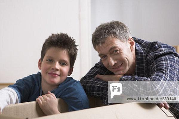 nahe Portrait Menschlicher Vater Sohn Bewegung Eigentumswohnung Pappschachtel Pappkarton Pappe neues Zuhause