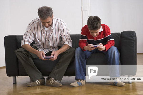 father and son sitting on sofa  playing with gameboy