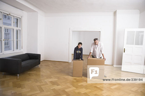 father and son with moving boxes in new home