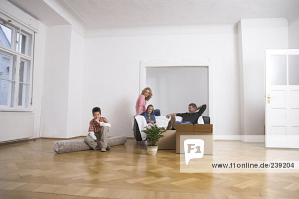 family in empty room  moving house into new home