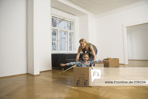mother pushing her daughter over the floor in moving box