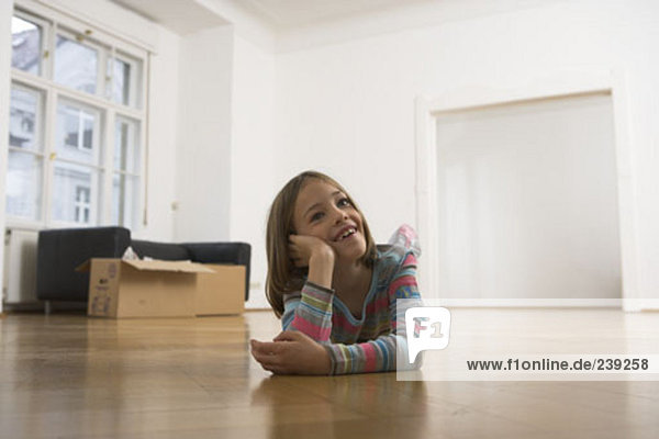 portrait of girl lying on floor in new home  cardboard boxes in background