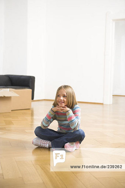 happy looking girl sitting on parquet floor after moving house