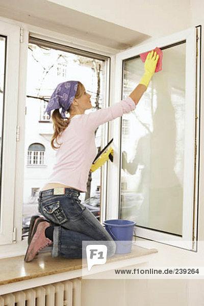 junge Frau junge Frauen kniend Fenster Reinigung Fensterbank