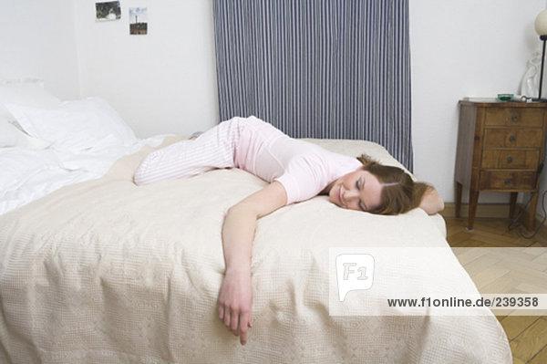 junge Frau mit einem Lächeln auf ihrem Gesicht auf Bett liegend