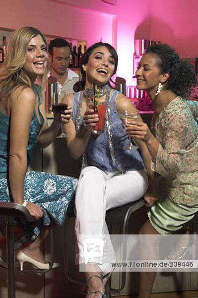 drei freudig Frauen Getränke zu halten Bar in einer Nacht heraus