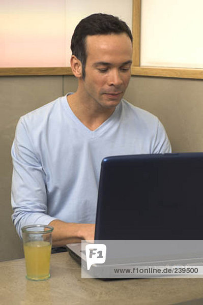 Porträt der jungen Mann  der arbeitet mit Notizbuch in cafe