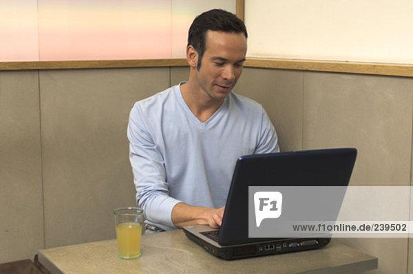Mann  der arbeitet mit Notebook-Computer im cafe