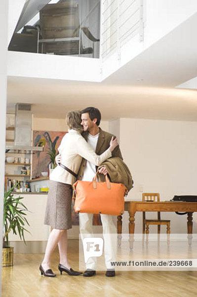 reifes Paar in Wohnung  Mann  hält orange bag